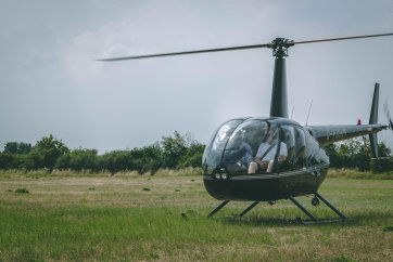 Hummingbird helicopters r44 helicopter setting off in field