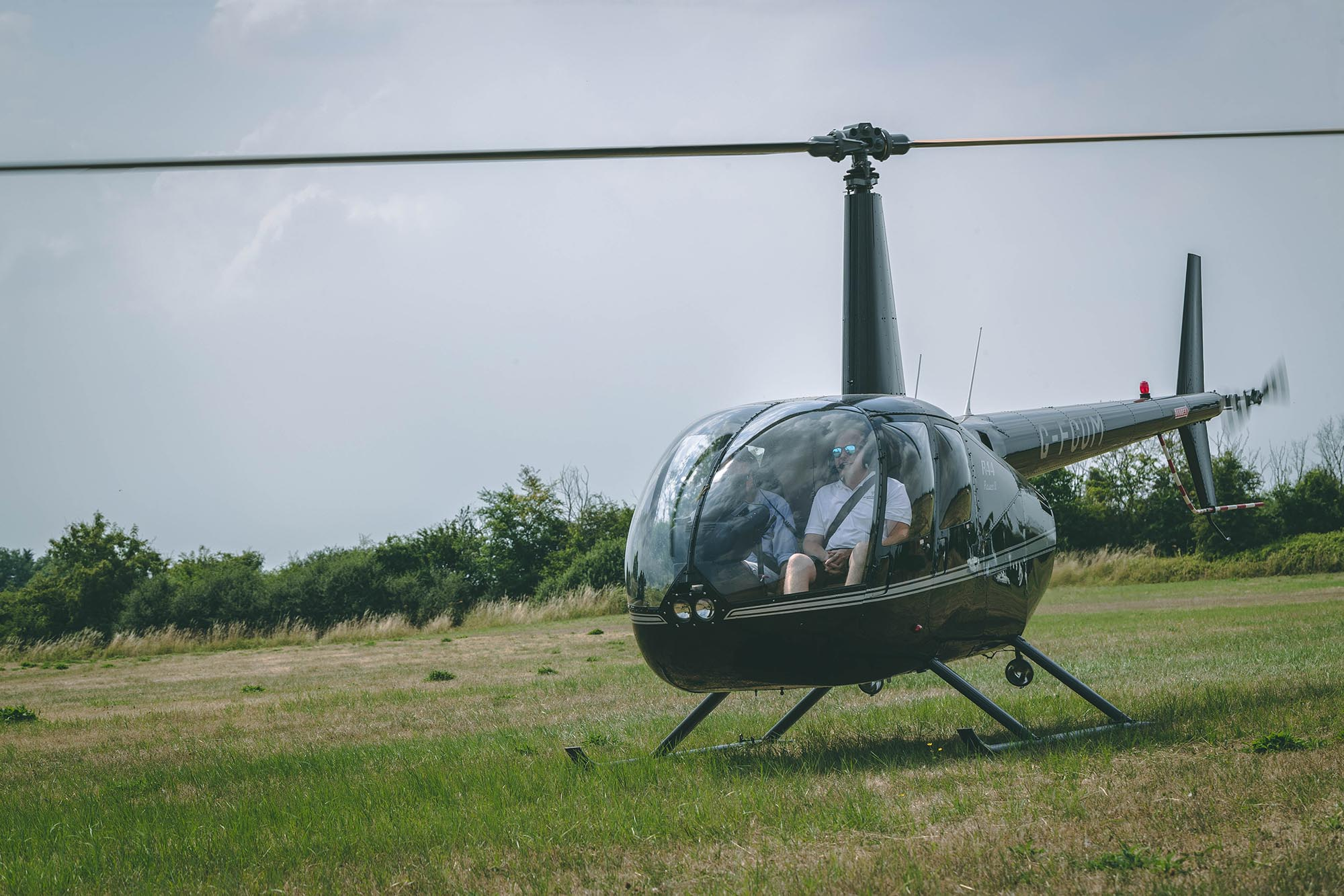Hummingbird helicopters r44 with pilots taking off in field
